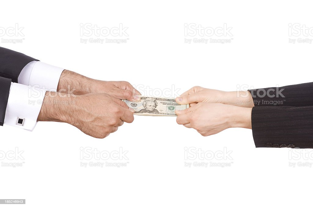 Man and woman's hands pulling on ends of twenty dollar bill stock photo