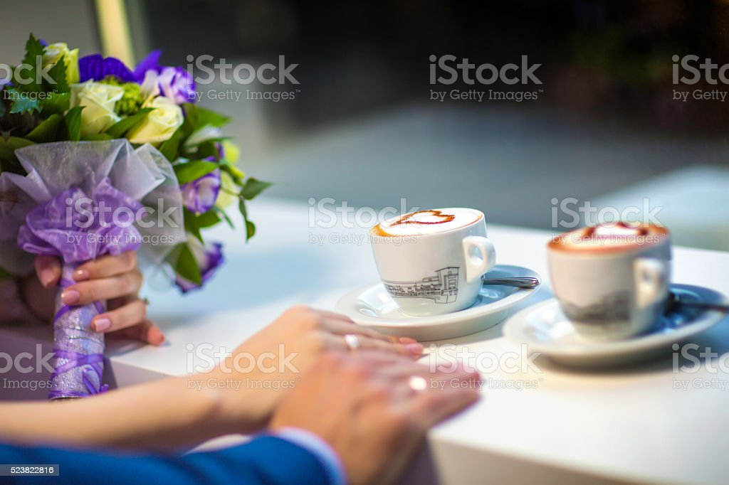 Man and woman's hands with espousal rings, coffee, wedding stock photo