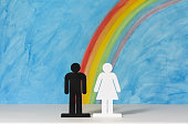 Man and women icons with a rainbow and blue sky