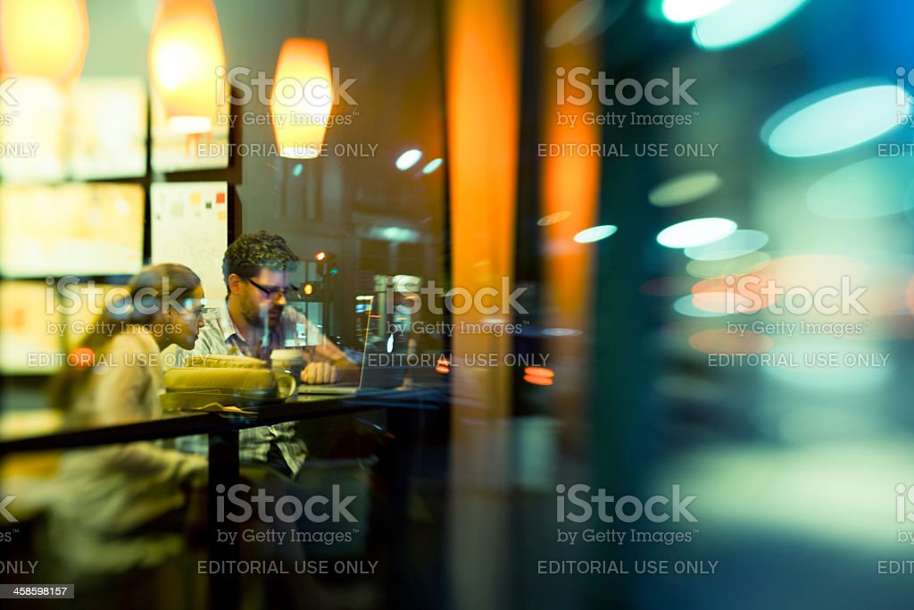 Man and women in the Starbucks cafe stock photo