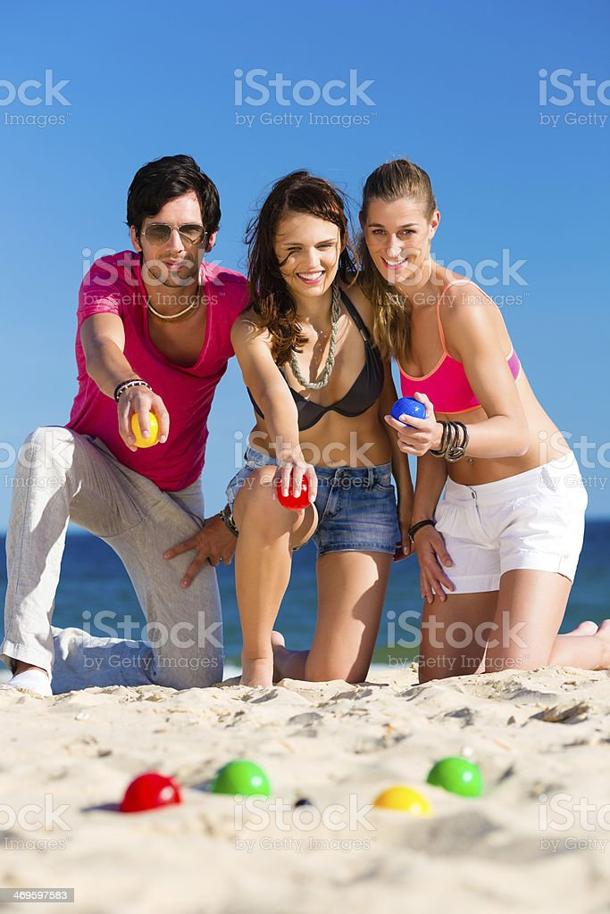 Man and women playing boule on beach stock photo
