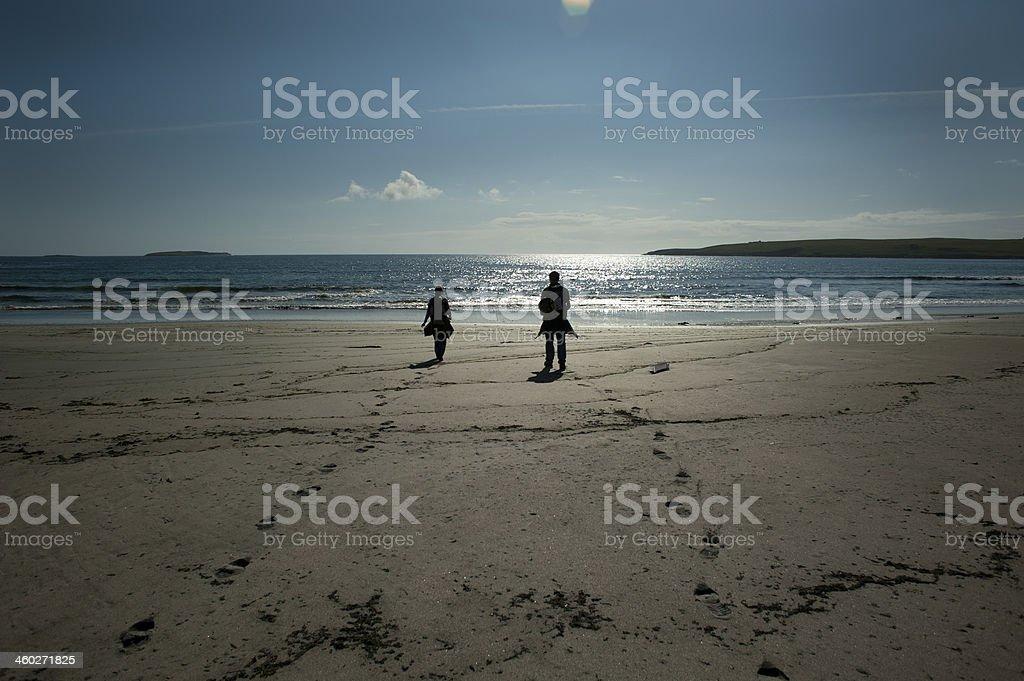 Man and Women walking on the beach stock photo