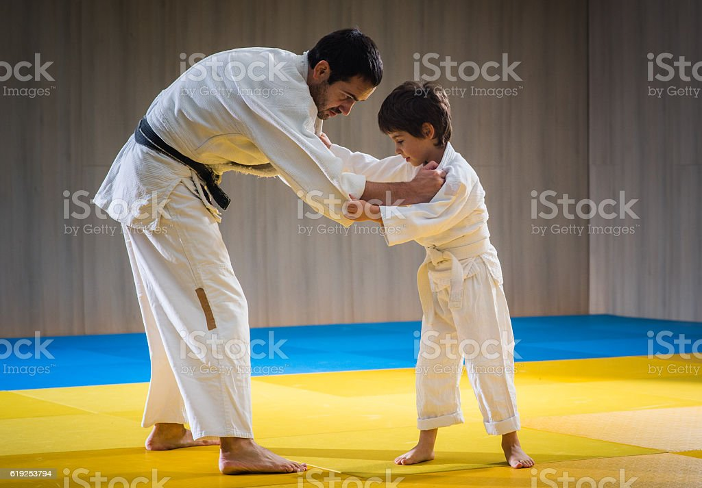 Man and young boy are training judo throw stock photo