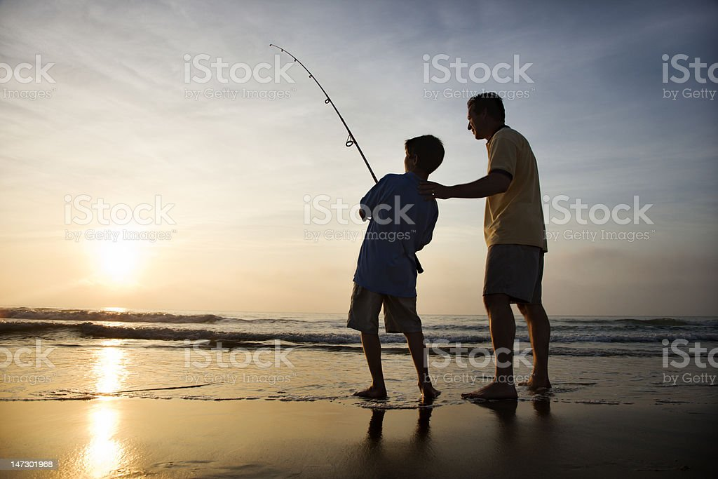 Man and young boy fishing in surf royalty-free stock photo