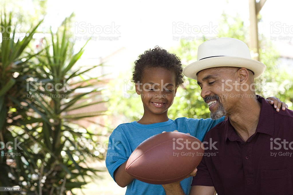 Man and young boy holding a football outdoors royalty-free stock photo