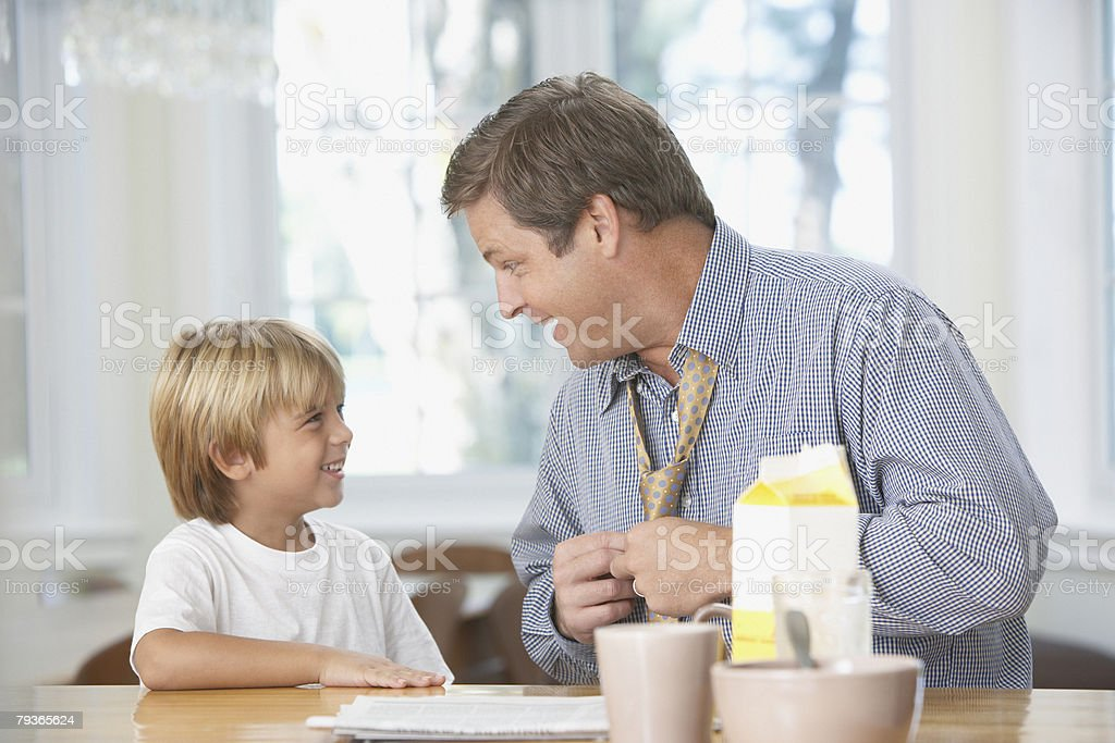 Man and young boy in kitchen bonding royalty-free stock photo