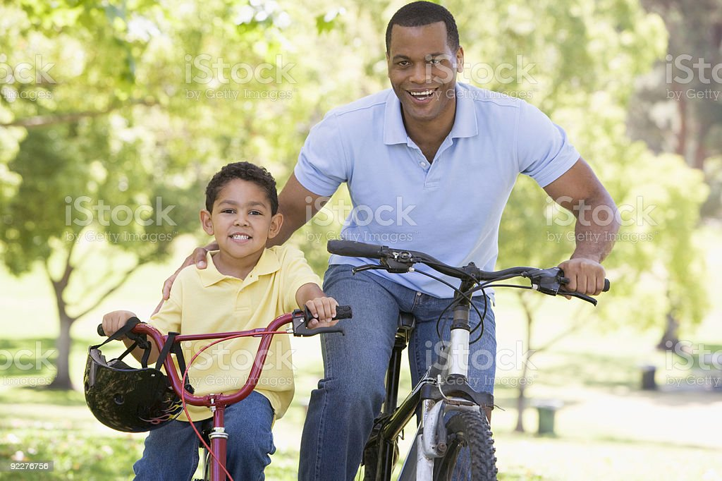 Man and young boy on bikes outdoors smiling royalty-free stock photo