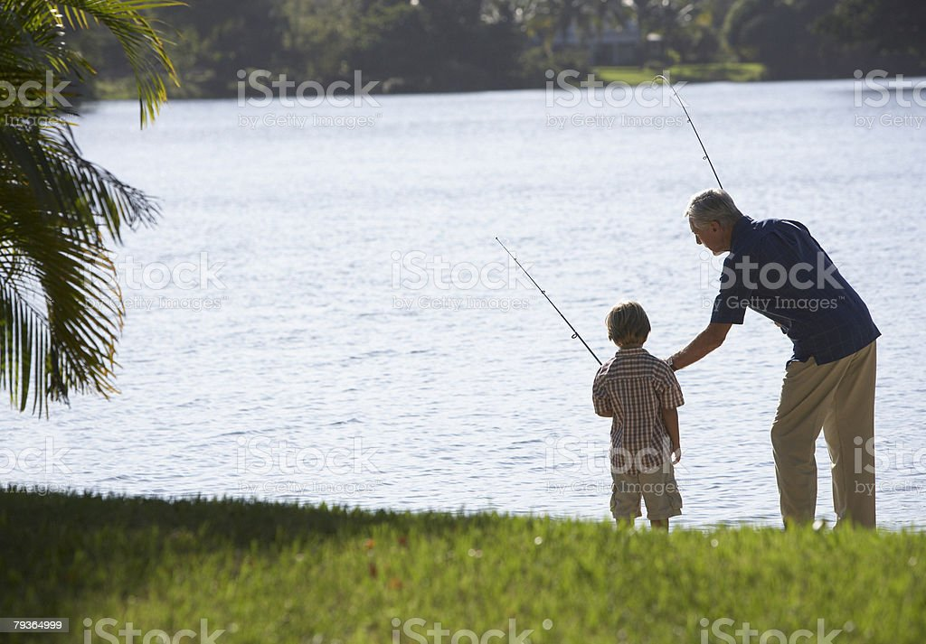 Man and young boy outdoors at park fishing in a lake stock photo