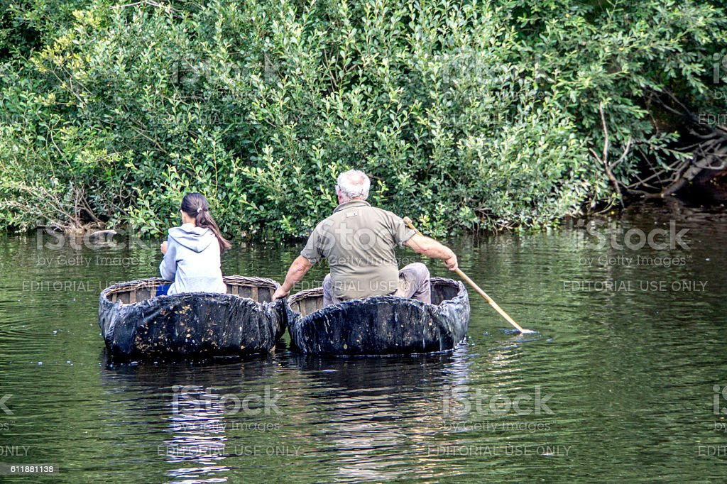 Man and young girl paddling Welsh coracle boats stock photo