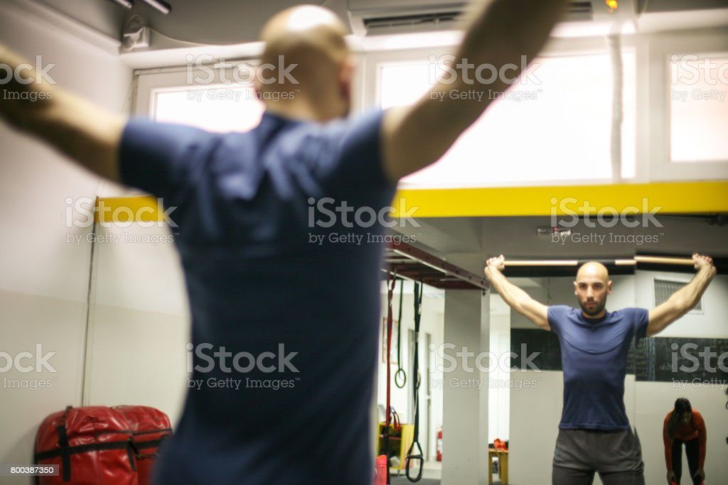Man and young woman preparing for workout in the gym. stock photo