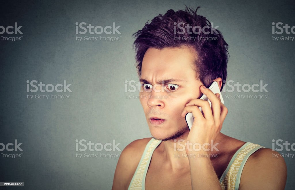 man annoyed, frustrated, pissed of by someone listening on his mobile phone stock photo