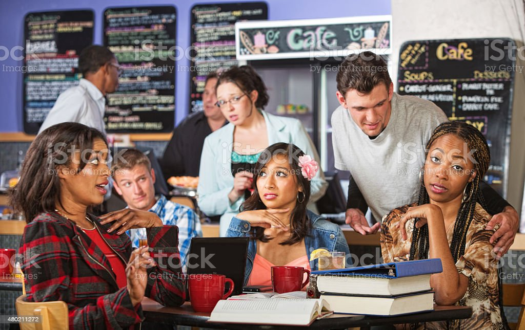 Man Annoying Students in Cafe stock photo