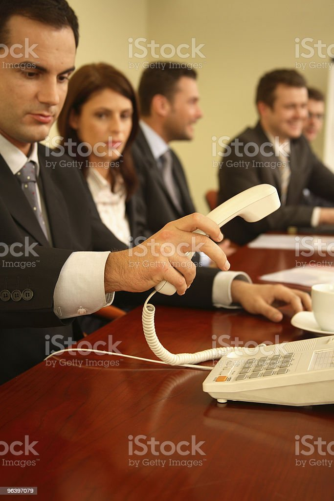 Man Answering Phone in Meeting royalty-free stock photo