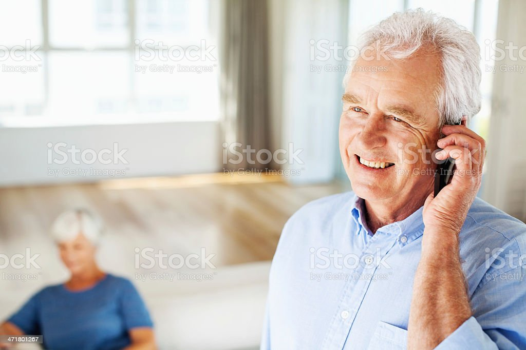 Man Answering Smart Phone With Woman Sitting In Background royalty-free stock photo