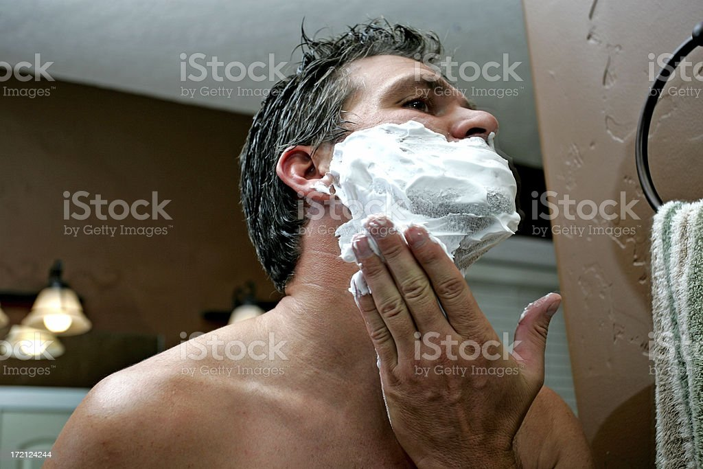 A man applying a shaving cream to his face stock photo