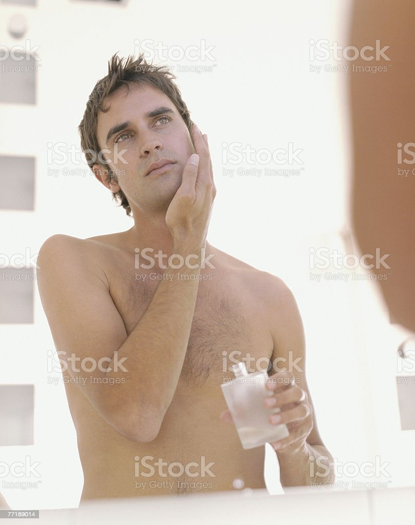 A man applying aftershave royalty-free stock photo