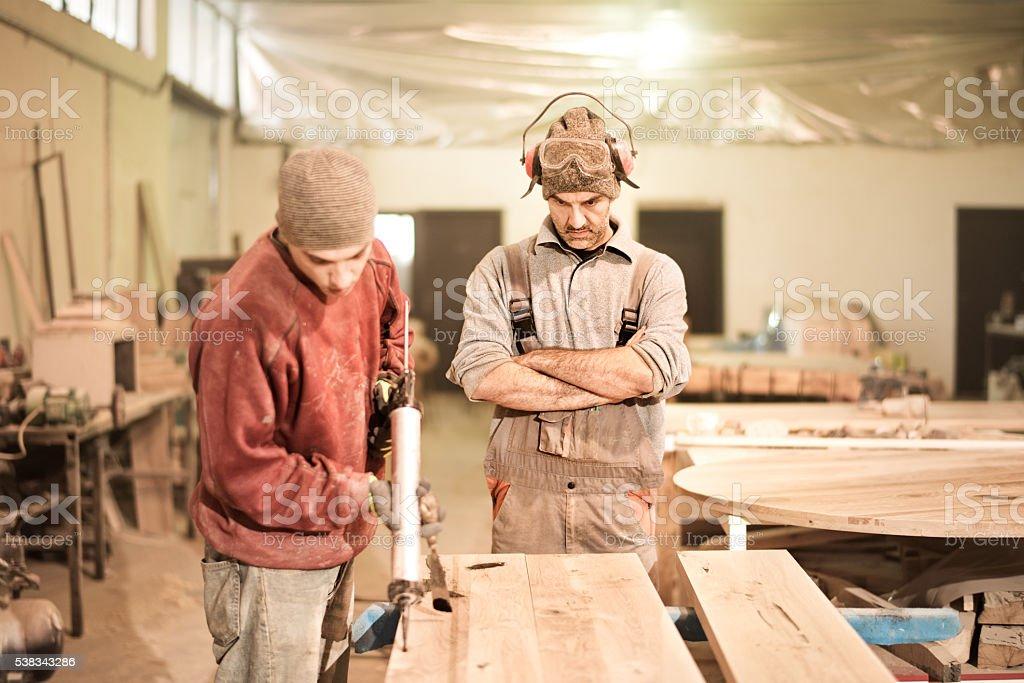Man applying glue on furniture parts stock photo