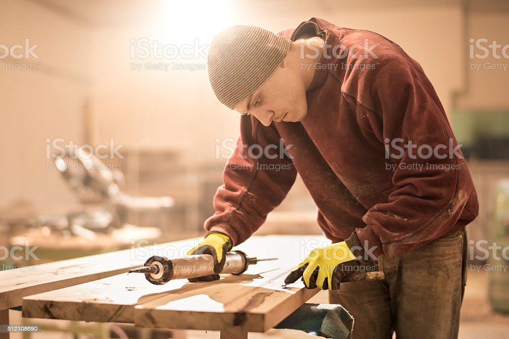 Man applying glue on wooden plank stock photo