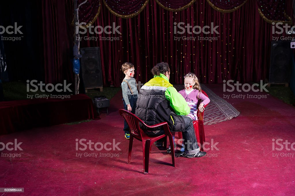 Man Applying Make Up to Girls Face on Empty Stage stock photo