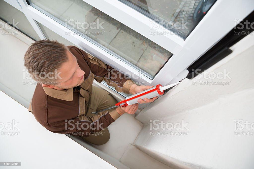 Man Applying Silicone Sealant With Gun stock photo