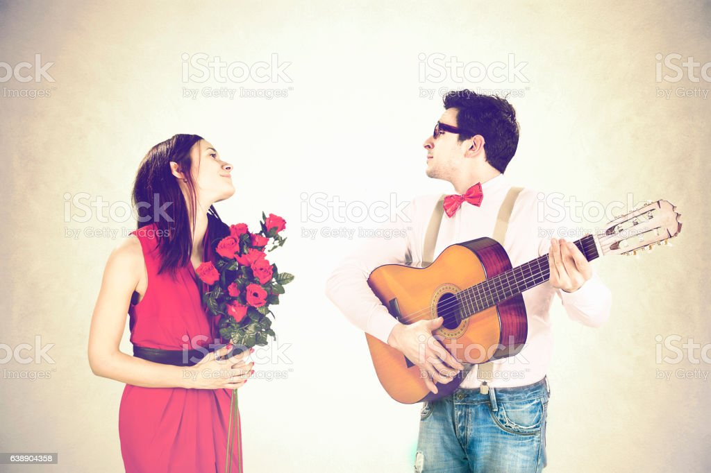 Man approaching woman playing a love song, serenade stock photo