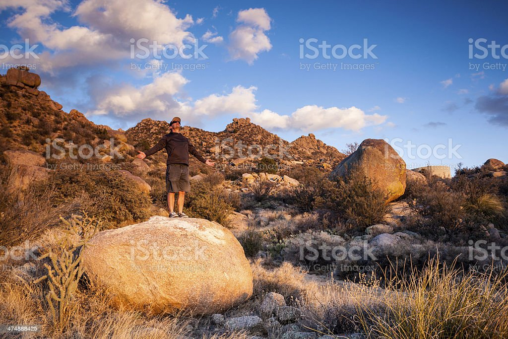 man arms spread wide and southwest landscape sunset royalty-free stock photo