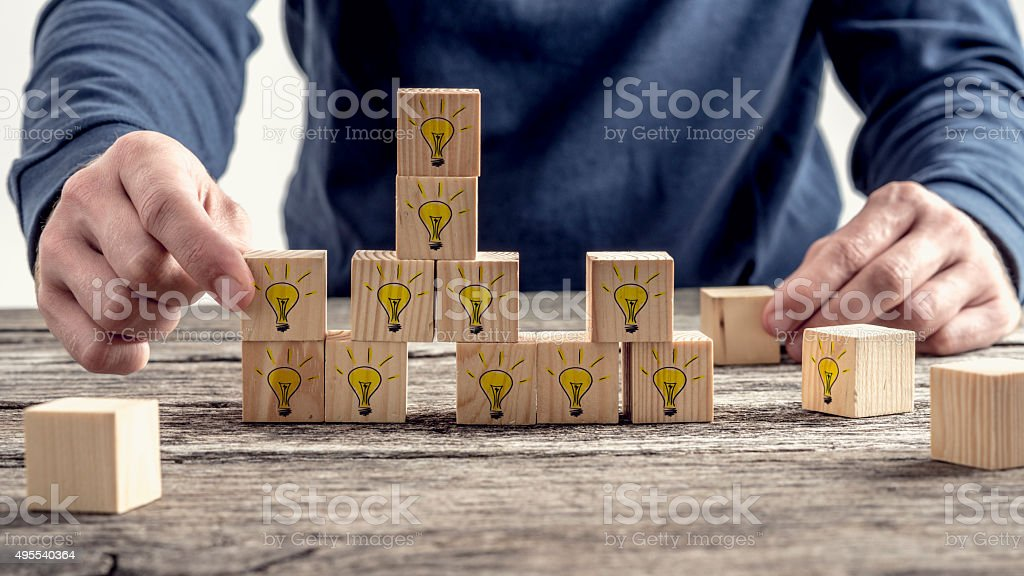 Man arranging wooden blocks with hand drawn yellow lightbulbs stock photo