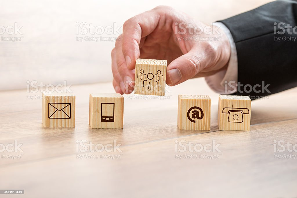 Man Arranging Wooden Cubes with Contact Symbols stock photo