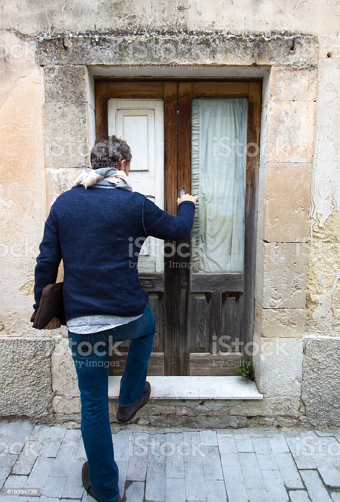 Man Arriving Home at Small Old Wood Door, Southern Europe stock photo