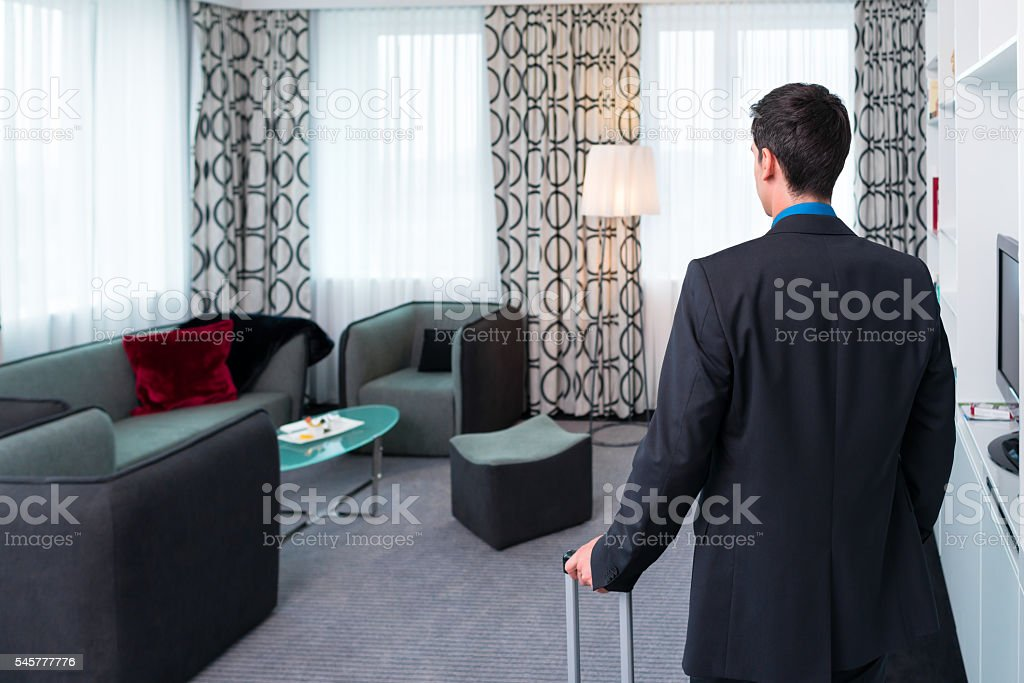 Man arriving in hotel room stock photo