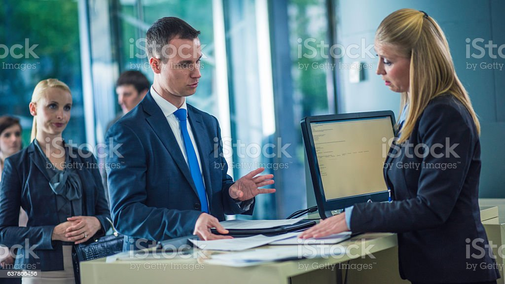 Man asking questions at a bank counter stock photo