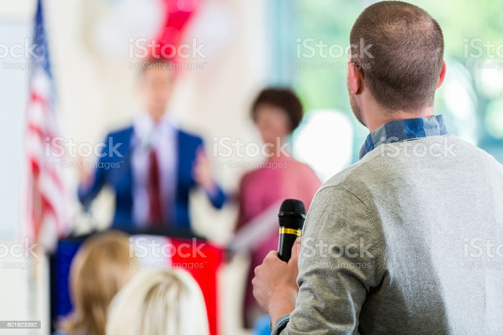 Man asking questions during political town hall meeting stock photo
