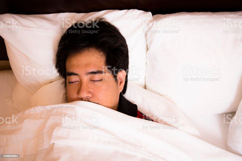 Man asleep in comfortable hotel room bed. stock photo