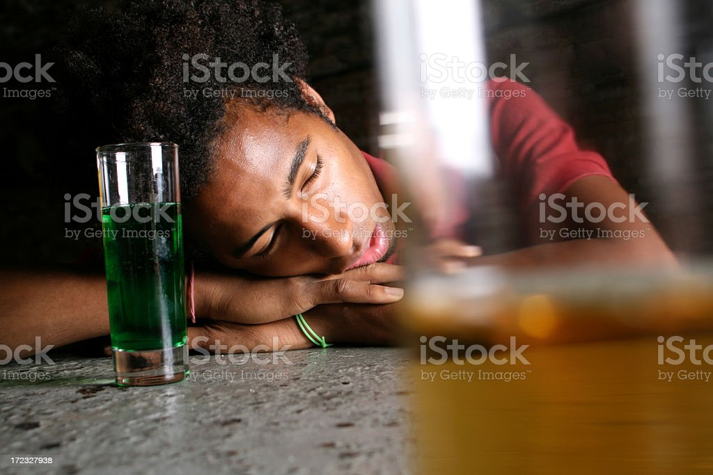 Man asleep in front of two alcoholic beverages royalty-free stock photo