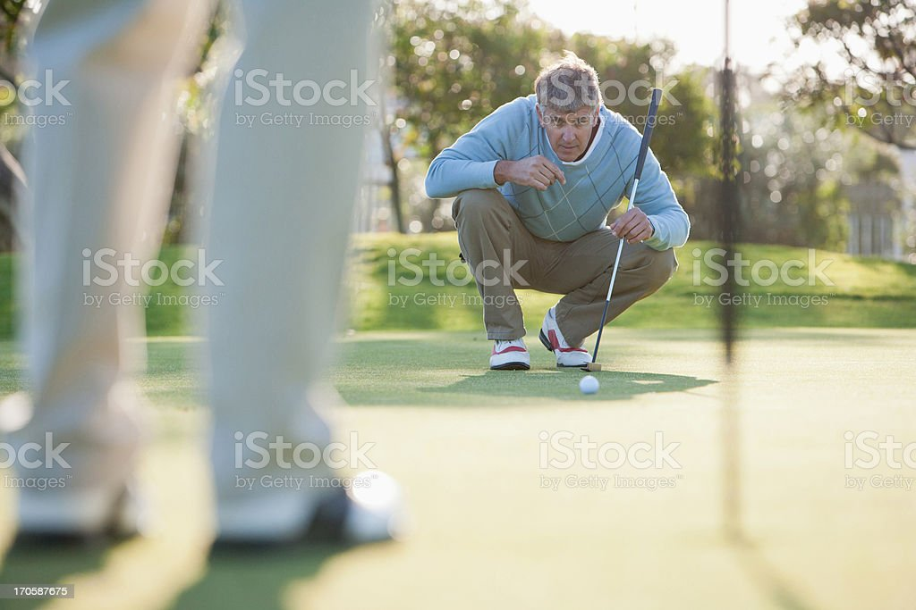 Man assessing play on putting green royalty-free stock photo