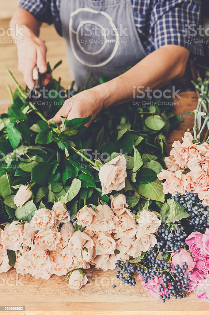 Man assistant in flower shop delivery make rose bouquet closeup stock photo