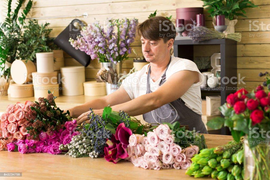 Small business. Male florist making rose bouquet in flower shop. Man...