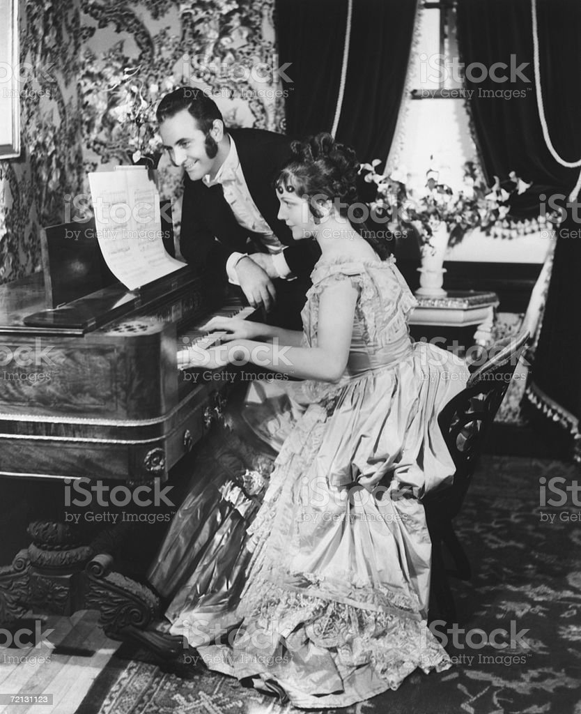 Man assisting woman playing on spinet (B&W) stock photo