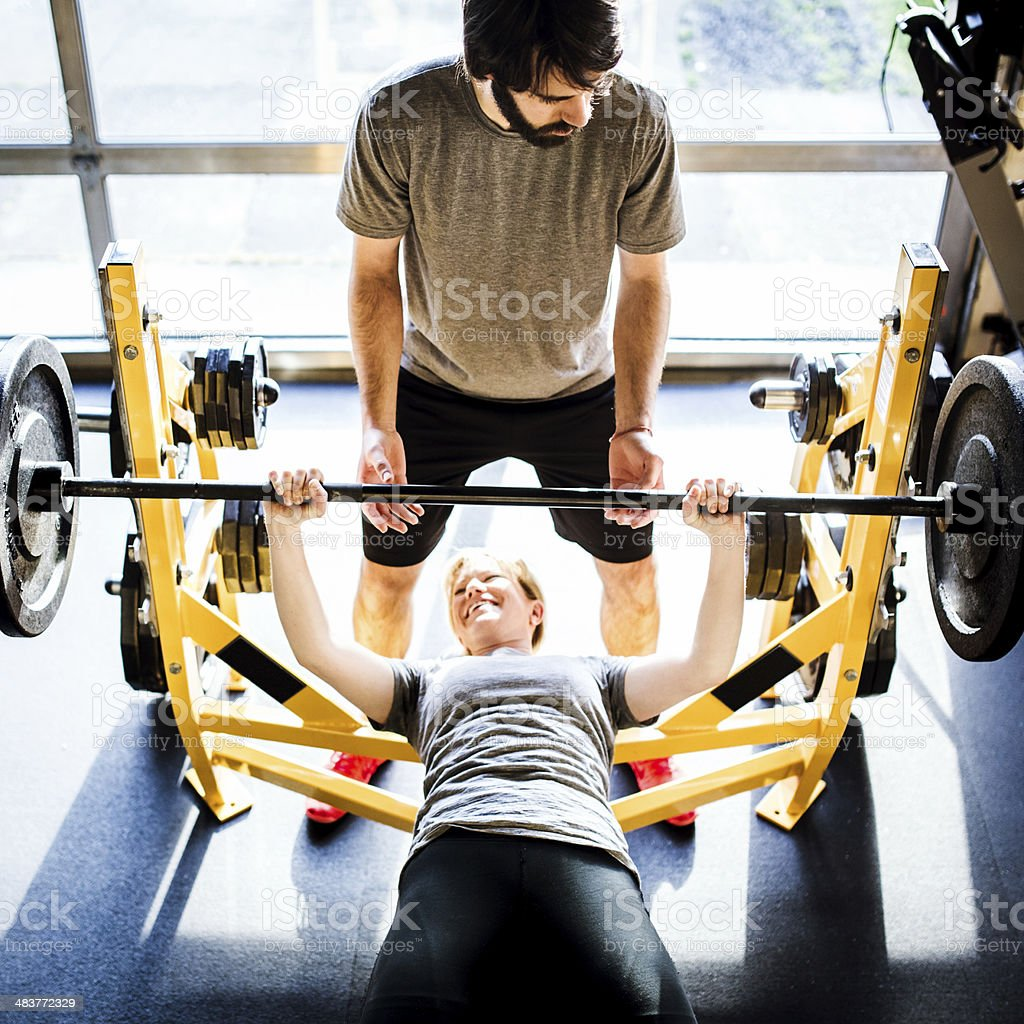 Man Assists with Bench Press stock photo