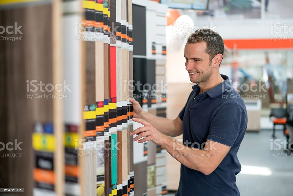 Man at a floor store looking at wood samples stock photo