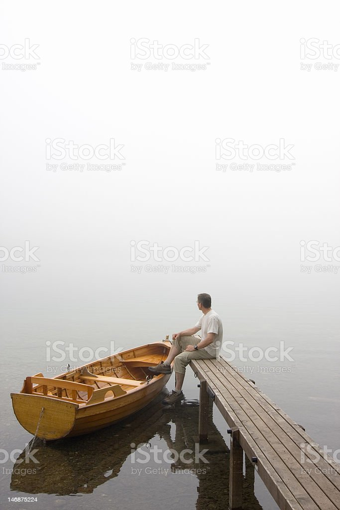 Man at a lake on misty morning royalty-free stock photo