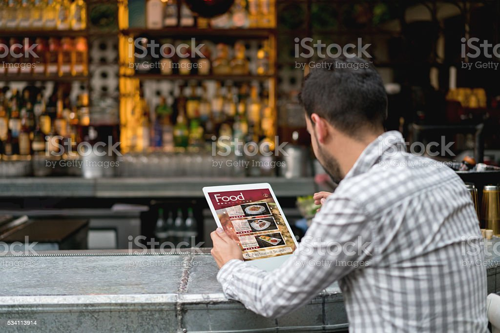 Man at a restaurant reading the menu stock photo