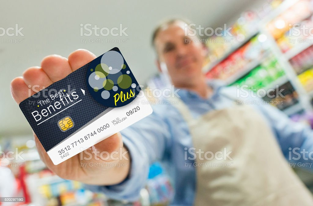 Man at a store holding a loyalty card stock photo