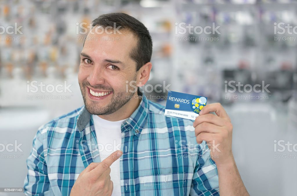 Man at a tech store holding a loyalty card stock photo