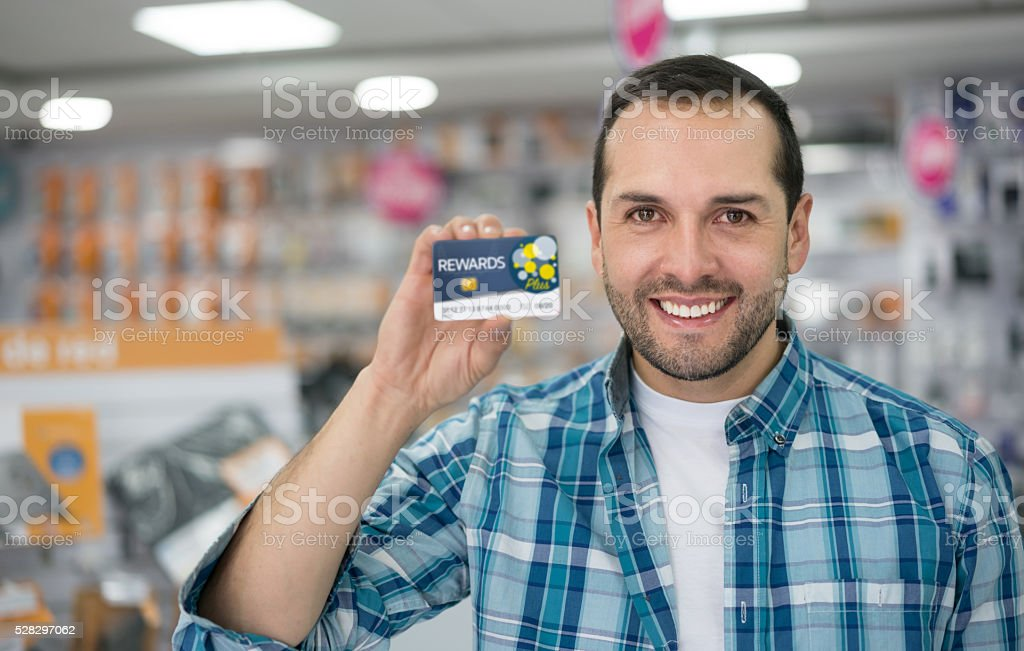 Man at a tech store holding a rewards card stock photo