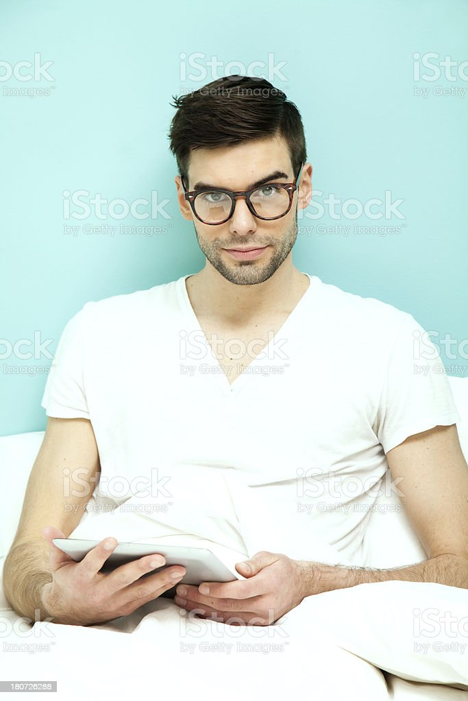 Man at bed with diigital tablet royalty-free stock photo