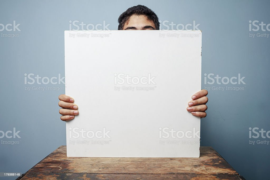 Man at desk hiding behind a white board royalty-free stock photo