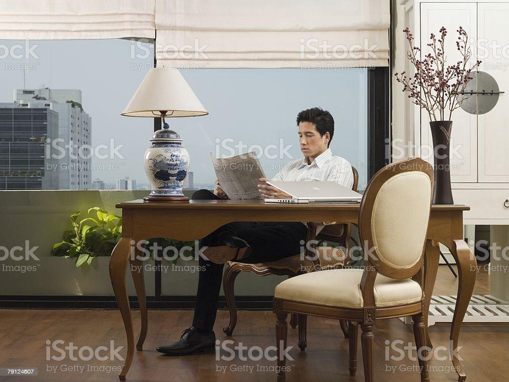 Man at desk reading newspaper royalty-free stock photo