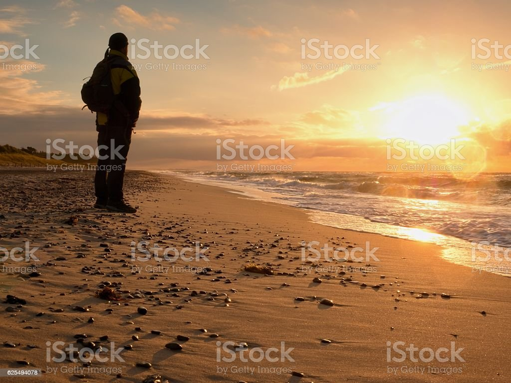Man at evening sea. Tourist in dark clothing and backpack stock photo