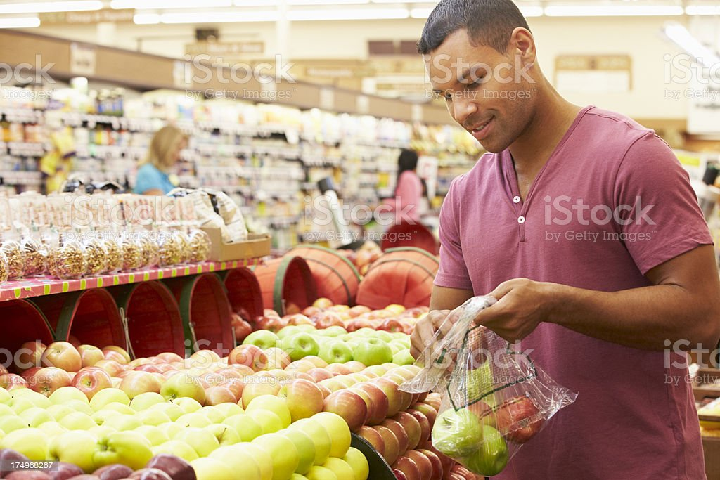 Man At Fruit Counter In Supermarket stock photo